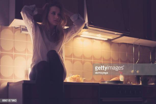 Sensual woman having problem with insomnia sitting on the kitchen counter