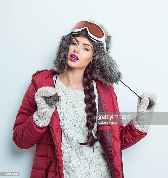 Sensual woman in winter outfit - puffer jacket, fur hat