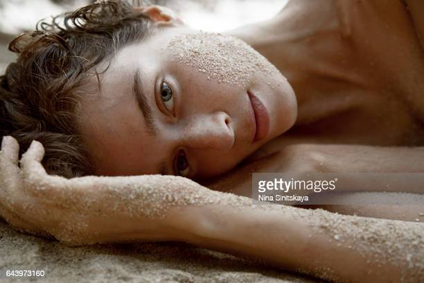 Sensual woman laying down on sand on the beach