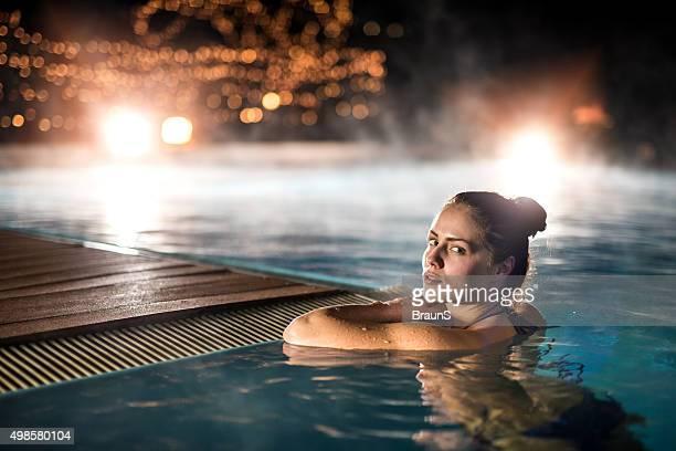 Mulher Sensual relaxante na piscina de inverno quente durante a noite.