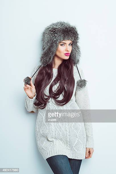 Sensual woman wearing a fur cap sand sweater