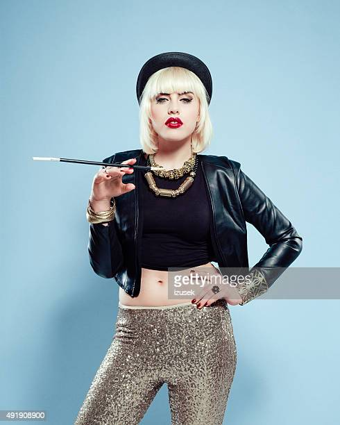 Sensual woman wearing leather jacket, gold trousers and bowler hat