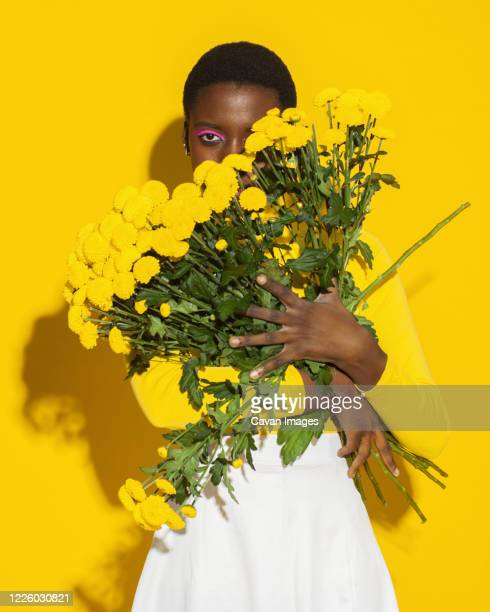 sensual woman with yellow flowers, total yellow - total look stock pictures, royalty-free photos & images
