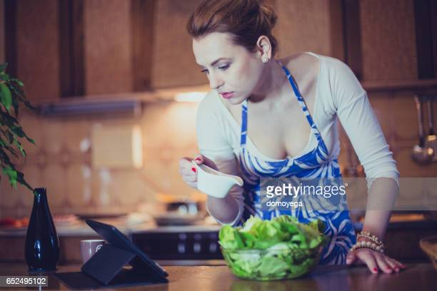 Sensual young girl reading recipes how to prepare healthy meal on her digital tablet