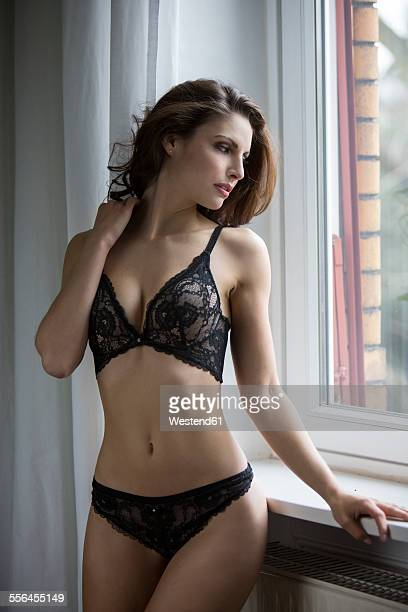 Sensual young woman in lingerie at the window