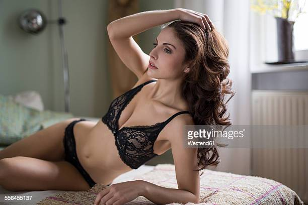 Sensual young woman in lingerie lying on couch