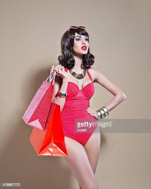 Sensualité jeune femme en maillot de bain tenant shopping sacs rouge