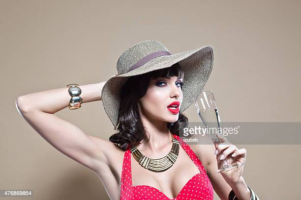 sensual young woman wearing sun hat holding a champagne glass - beige hat stock photos and pictures