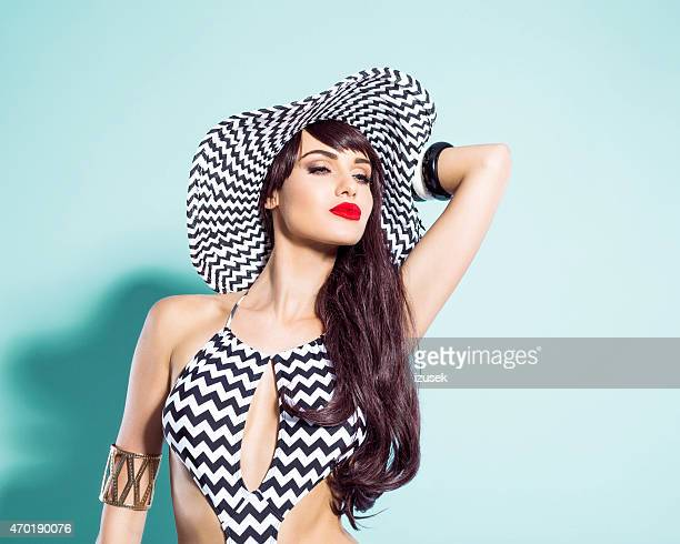 Sensual young woman wearing swimsuit and sunhat