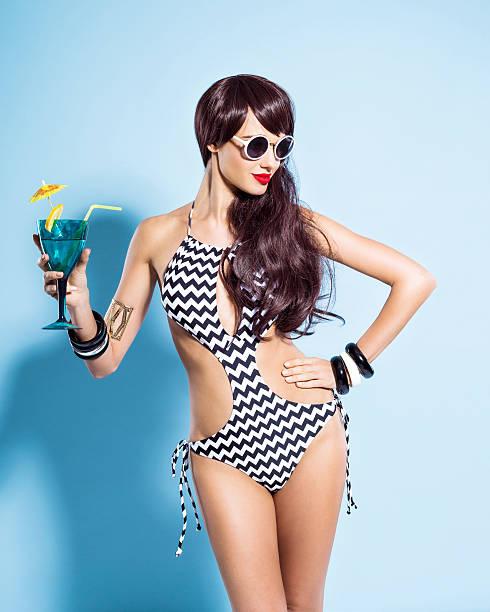 Sensualité jeune femme en maillot de bain tenant boire
