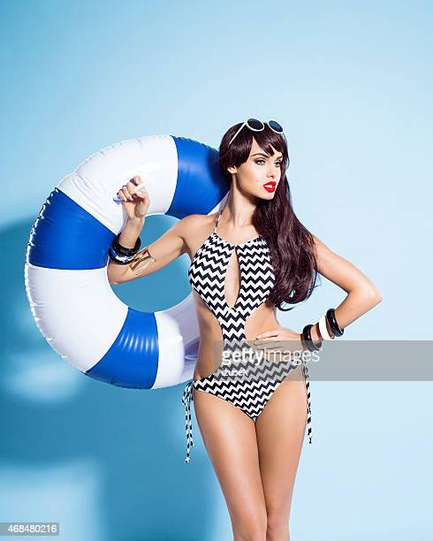 Sensual young woman wearing swimsuit holding lifebuoy