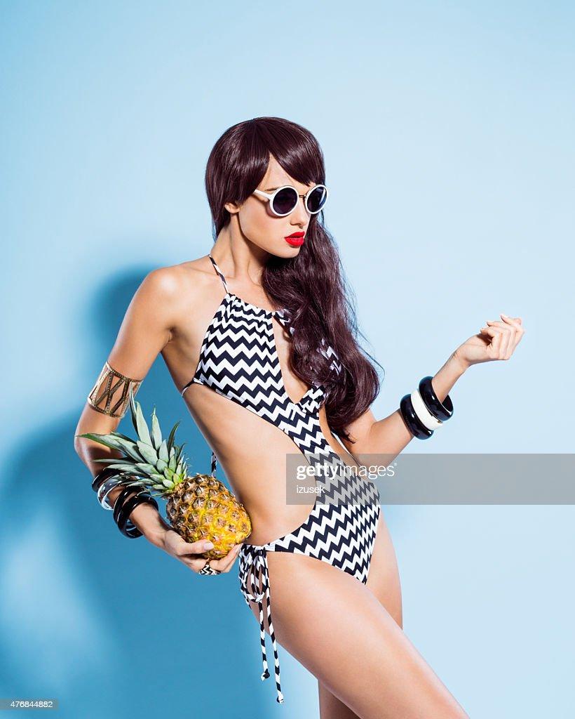 Sensualité jeune femme en maillot de bain tenant à l'ananas