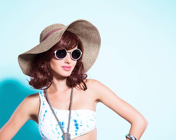 Sensualité jeune femme en maillot de bain, lunettes de soleil et sunhat