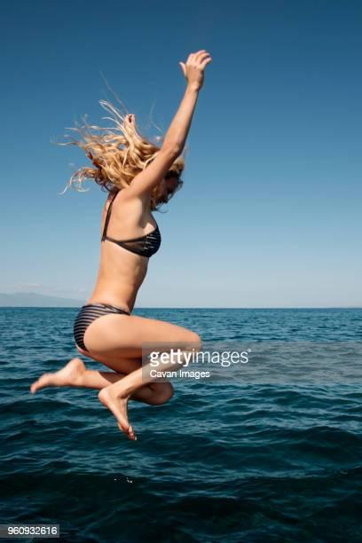 Sensuous woman in bikini diving in sea against clear blue sky