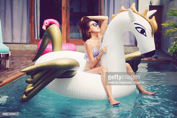 Sensuous Woman In Bikini Sitting On Unicorn Shape Inflatable Ring In Pool