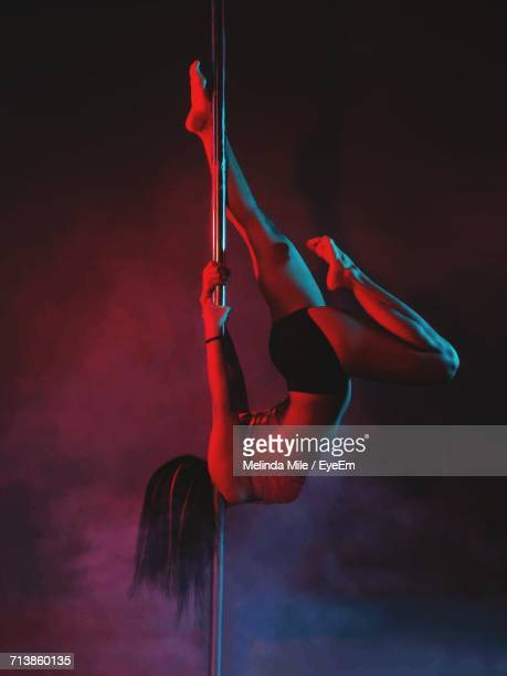 sensuous woman performing pole dance at nightclub - pole dance photos et images de collection