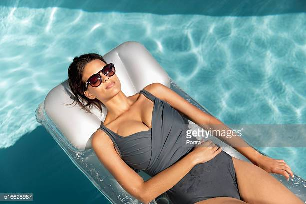 sensuous woman relaxing on pool raft - one piece swimsuit stock pictures, royalty-free photos & images