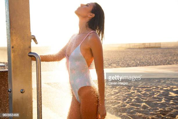 Sensuous woman taking shower at beach on sunny day