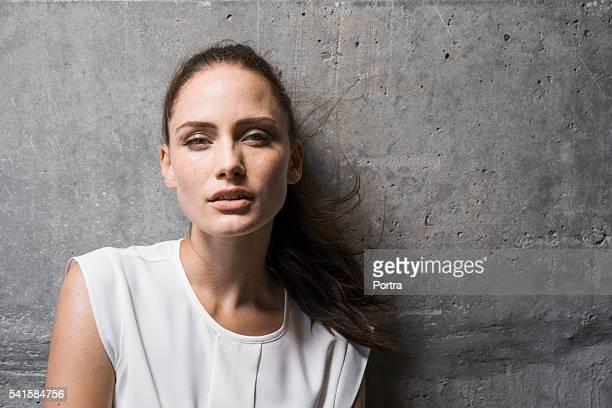 Sinnliche junge Frau gegen Wand