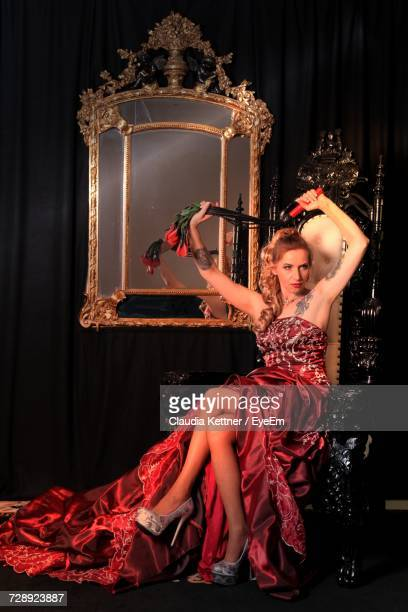 sensuous young woman in red dress holding whip while sitting on throne - women with whips stock pictures, royalty-free photos & images