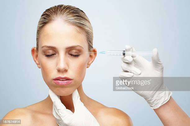 Sensuous young woman receiving Botox injection on face