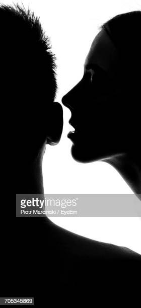 Sensuous Young Woman Whispering Into Man Ear Against White Background