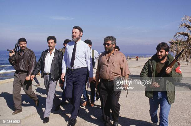 Sent by the Archbishop of Canterbury to Lebanon to negotiate for the release of Western hostages Terry Waite goes for a walk at the beach flanked by...