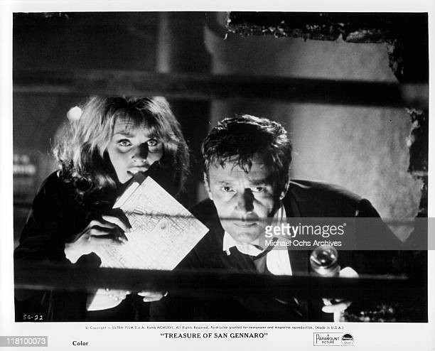 Senta Berger and Harry Guardino look forward with map and flashlight in a scene from the film 'Treasure of San Gennaro' directed by Dino Risi 1966