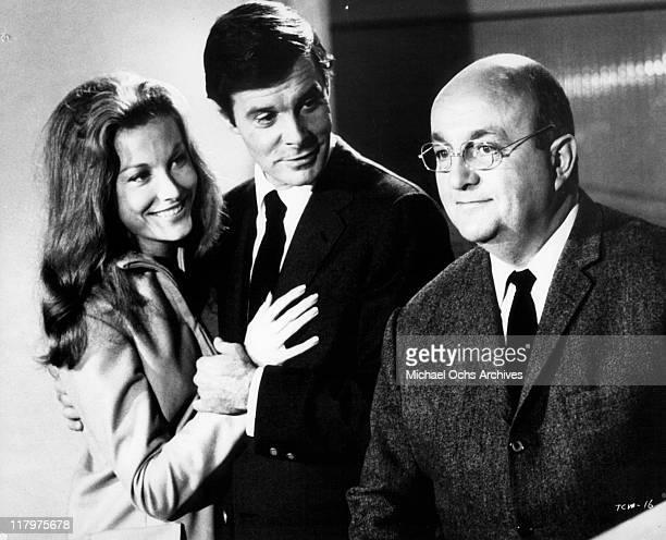 Senta Berger holds onto Louis Jourdan as Bernard Blier looks on in a scene from the film 'To Commit a Murder' 1967