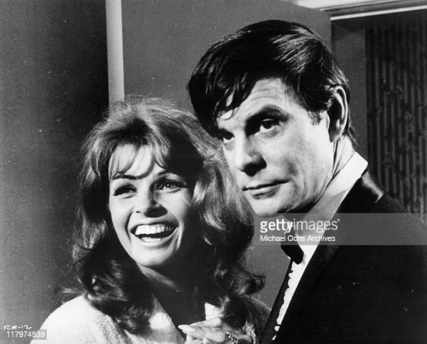 Senta Berger smiles while Louis Jourdan looks on in a scene from the film 'To Commit a Murder' 1967