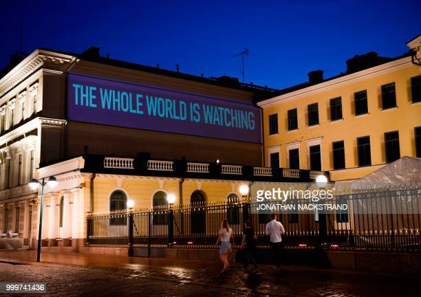 A sentence reading The Whole World is Watching is projected on the presidential palace on the eve of a summit between US President Donald Trump and...