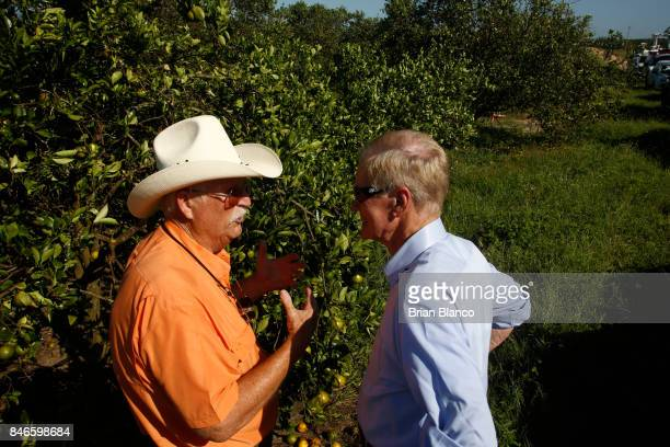 Sentor Bill Nelson right speaks with Vic Story as he tours the Story Grove orange grove where large numbers of oranges sit on the ground in the wake...