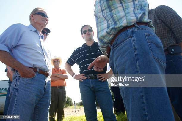 Sentors Marco Rubio center and Bill Nelson left tour the Story Grove orange grove where large numbers of oranges sit on the ground in the wake of...
