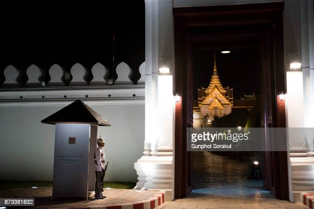 A sentry guard in front of Wiset Chaisri gate with the roof of Chakri Maha Prasat