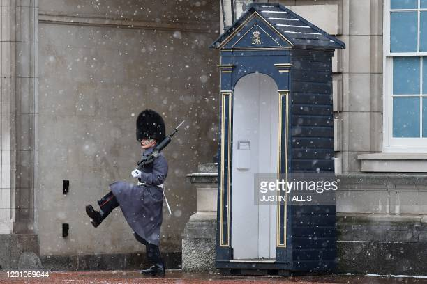 Sentry of the Scot's Guards stands on duty in the snow outside Buckingham Place in central London on February 9, 2021. - Cold weather swept across...