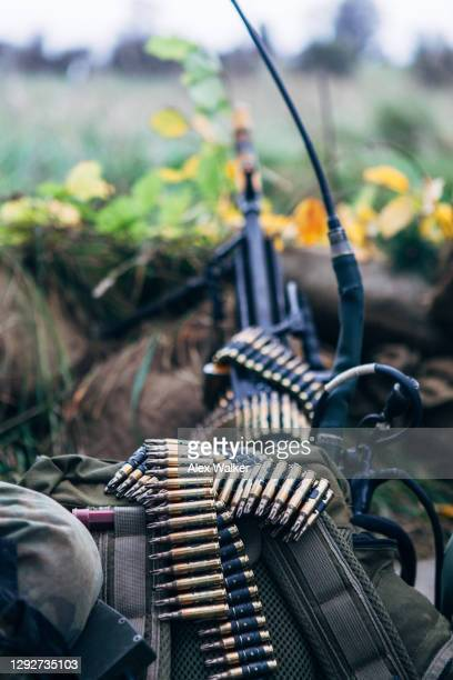 sentry outpost with a belt of black training rounds resting on a backpack - gunman stock pictures, royalty-free photos & images