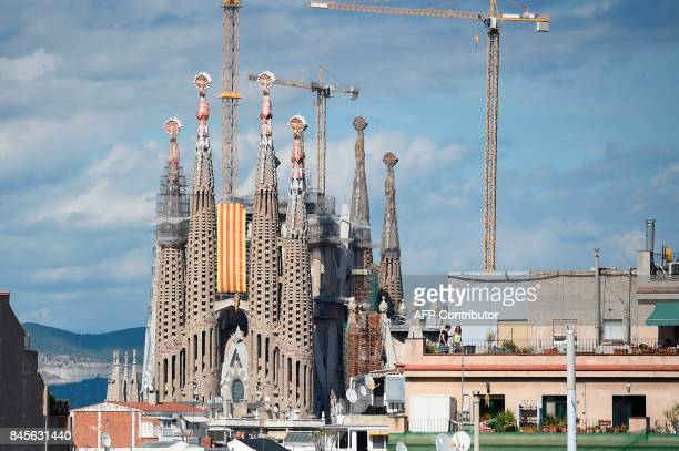 A Senyera flag hangs from the Sagrada Familia basilica on September 11 2017 in Barcelona during the National Day of Catalonia the Diada Hundreds of...