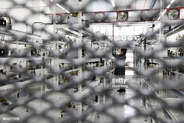 Seo Heejin is seen behind a barrier as she inspects applicationspecific integrated circuit devices and power units manufactured by Bitmain...