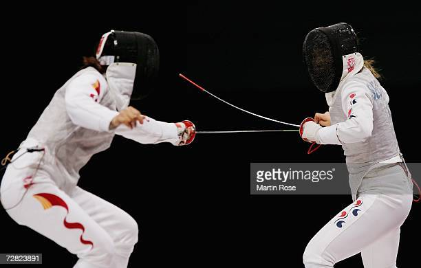 Seo Mi Jung of Republic of Korea competes with Su Wanwen of China in the Women's Team Foil Gold Medal match during the 15th Asian Games Doha 2006 at...