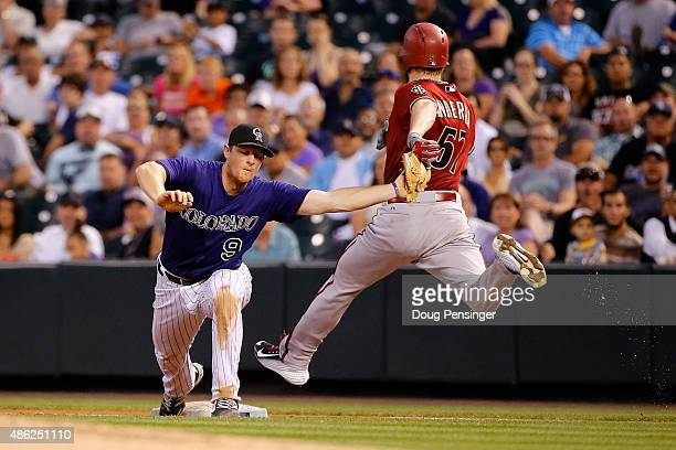 Seocnd baseman DJ LeMahieu of the Colorado Rockies gets a put out at first base on Chase Anderson of the Arizona Diamondbacks to complete a double...