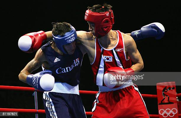 Seok Hwan Jo of Korea and Benoit Gaudet of Canada in action during the men's boxing 57 kg preliminary bout on August 20, 2004 during the Athens 2004...