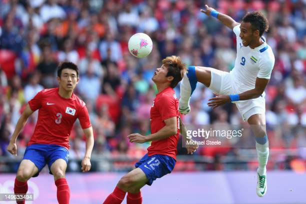 Seokho Hwang of Korea Republic is challenged by Pierre Aubameyang of Gabon during the Men's Football first round Group B Match between Korea Republic...