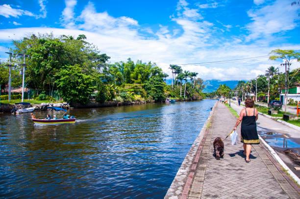 Señora paseando al perro y gente disfrutando del río en un día de sol. Paraty, Brasil.