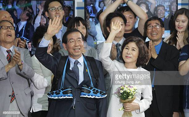 Seoul city mayorelect Park WonSoon of the main opposition party New Politics Alliance for Democracy celebrates and his wife Kang NanHee wave to...