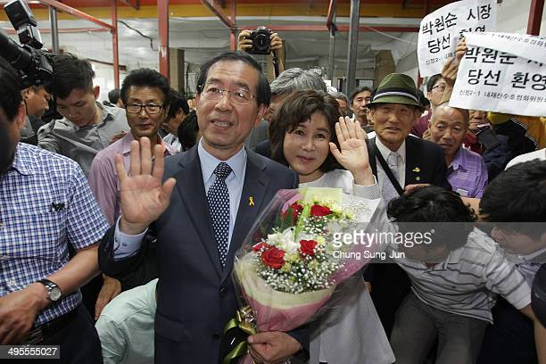 Seoul city mayorelect Park WonSoon of the main opposition party New Politics Alliance for Democracy celebrates holds flowers with his wife Kang...