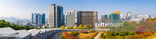 seoul city walls overlooked by downtown skycraper cityscape panorama korea - seoul stock pictures, royalty-free photos & images