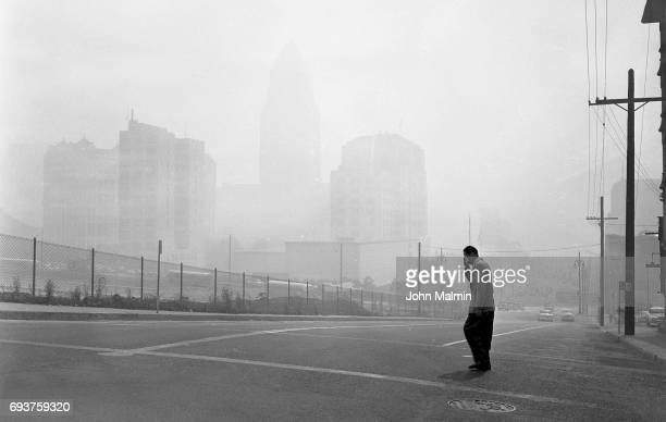 Buildings in Los Angeles Civic Center are barely visible in picture looking east at 1st and Olive Sts at 11 am when smog was at its peak Visible...