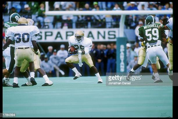 Flanker Raghib Ismail of the Notre Dame Fighting Irish runs down the field during a game against the Michigan State Spartans at Spartan Stadium in...