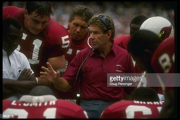 Phoenix Cardinals head coach Joe Bugel confers with his team during a game against the Washington Redskins at Sun Devil Stadium in Tempe Arizona The...