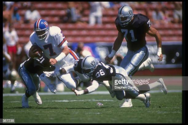 Quarterback John Elway of the Denver Broncos gets tackled by several Los Angeles Raiders players during a game at the Coliseum in Los Angeles...